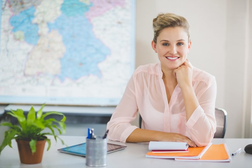 Portrait of teacher sitting in classroom at school